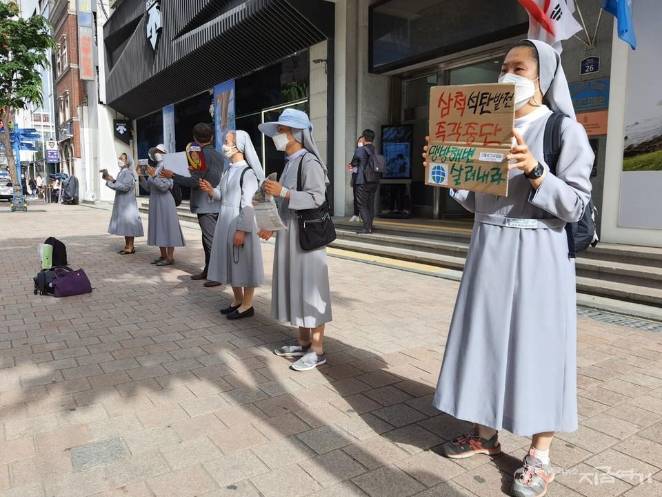 미사 뒤 명동 거리에서 손팻말로 기후위기 심각성을 알리는 수도자들. ⓒ김수나 기자<br>