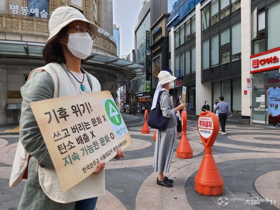 미사 뒤 명동 거리에서 손팻말로 기후위기 심각성을 알리는 참가자들. ⓒ김수나 기자<br>