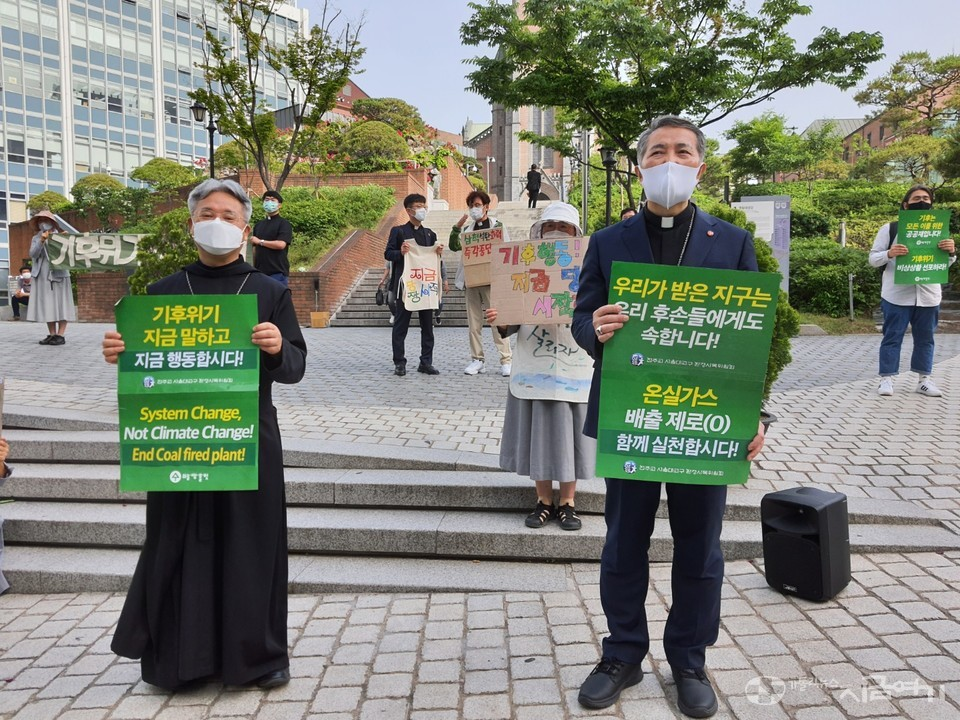 명동 성당 들머리에서 손팻말을 들고 있는 박현동 아빠스(왼쪽)와 문창우 주교. ⓒ김수나 기자